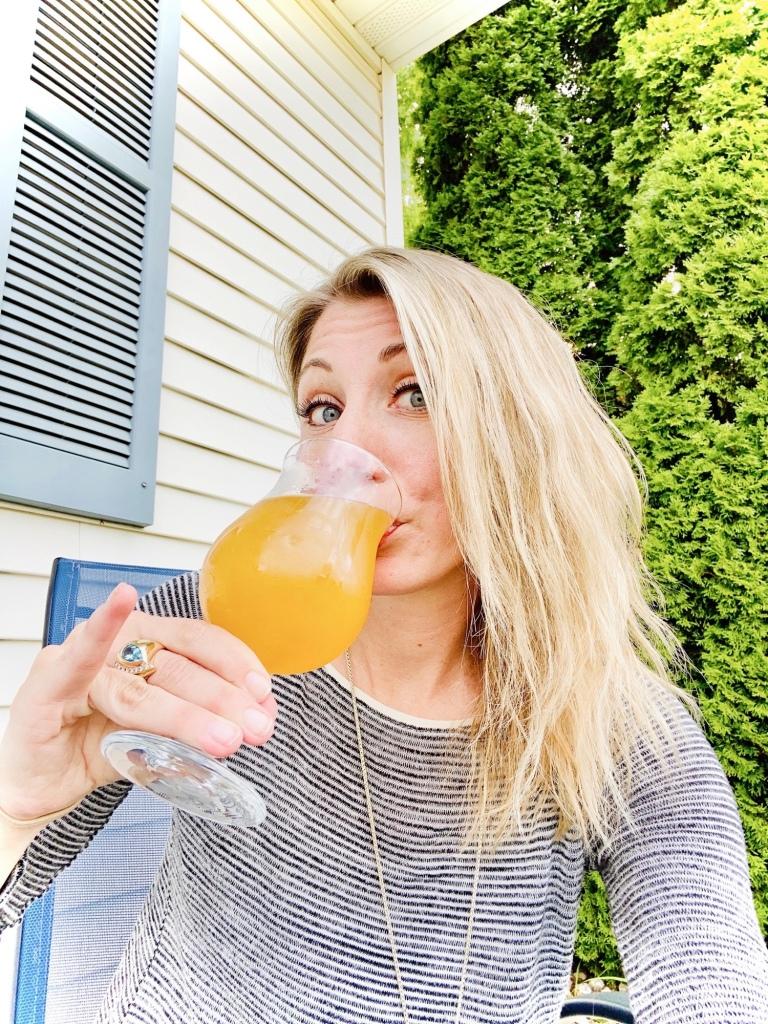 Jess drinking beer in a fancy glass