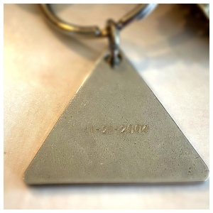 Side of a triangular keychain engraved with the date 11/21/2004