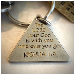 A triangular keychain engraved with the Bible verse Joshua 1:9