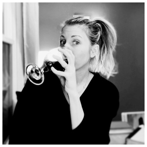 Black and white image of Jess looking at the camera while drinking