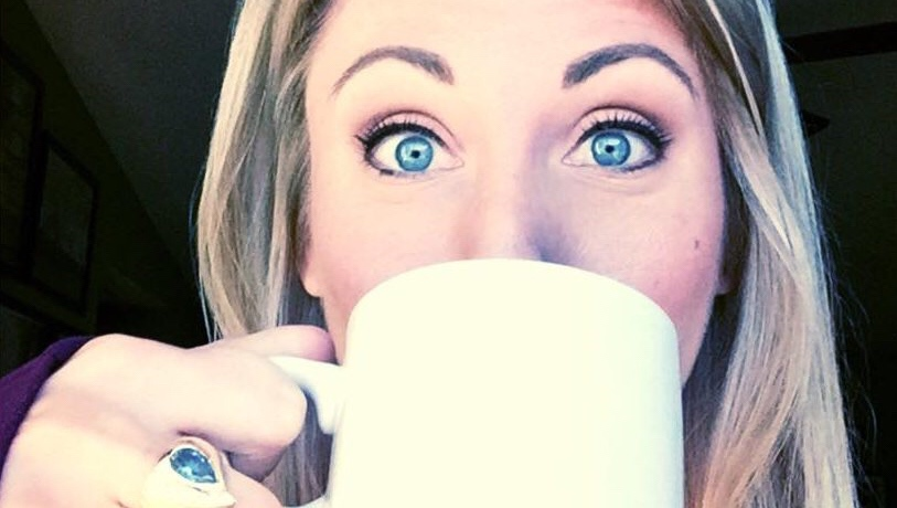 Jessica drinking from a white coffee mug, her blue eyes peering over the top