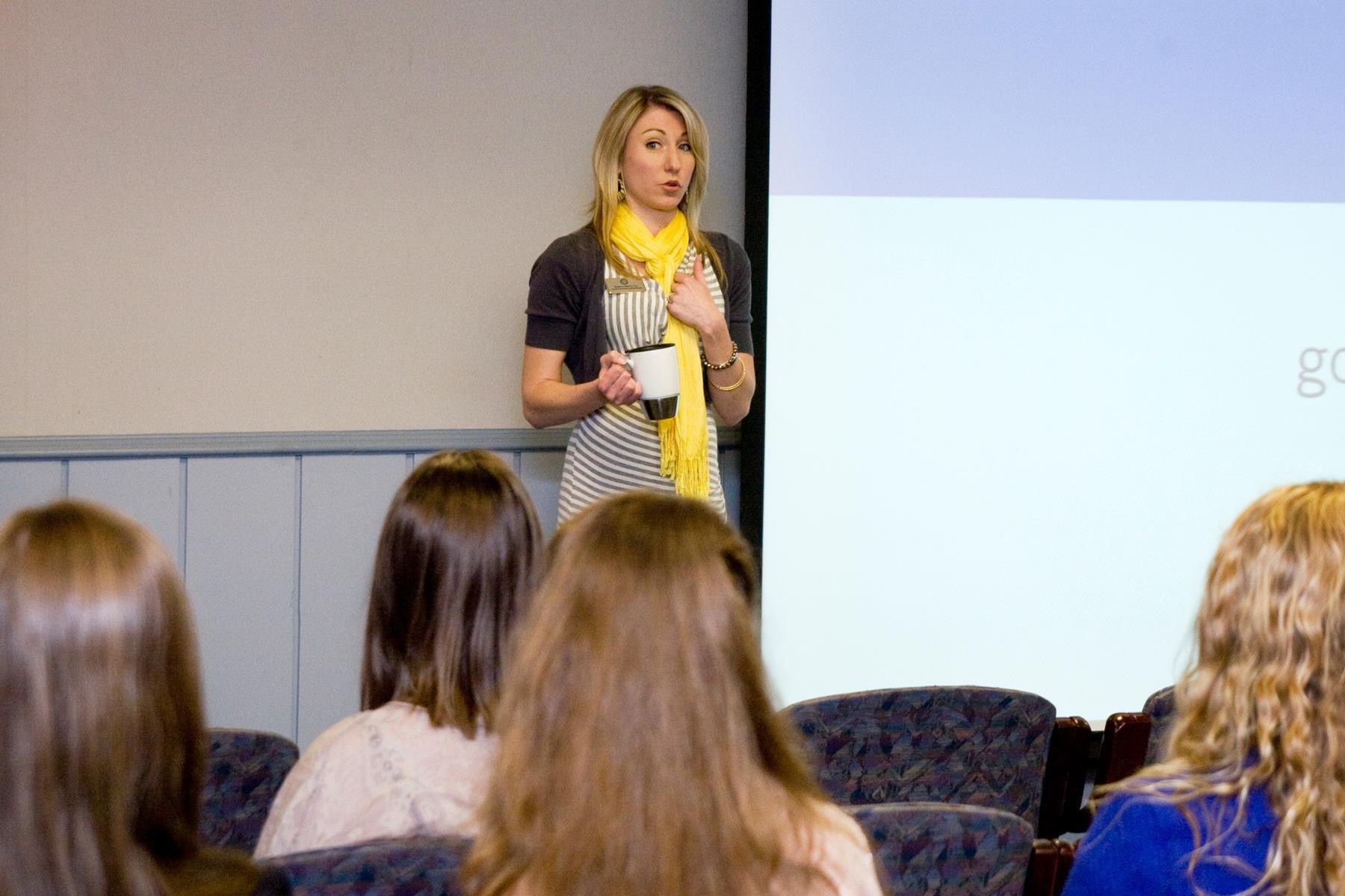 Blonde woman in a yellow scarf giving a standing presentation in front of a screen with a coffee mug in her hand