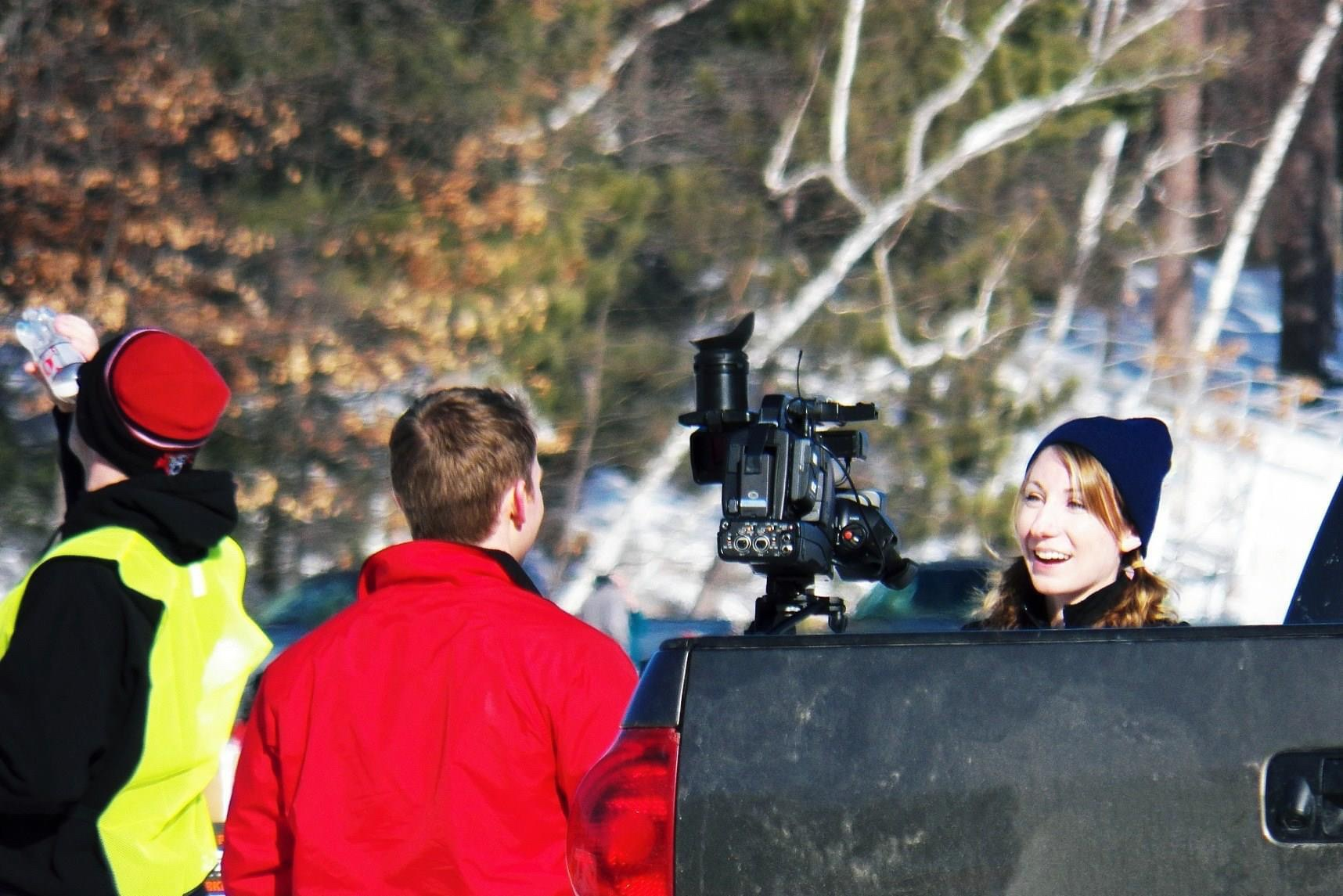 blonde woman in a ski hat being interviewed by a TV crew