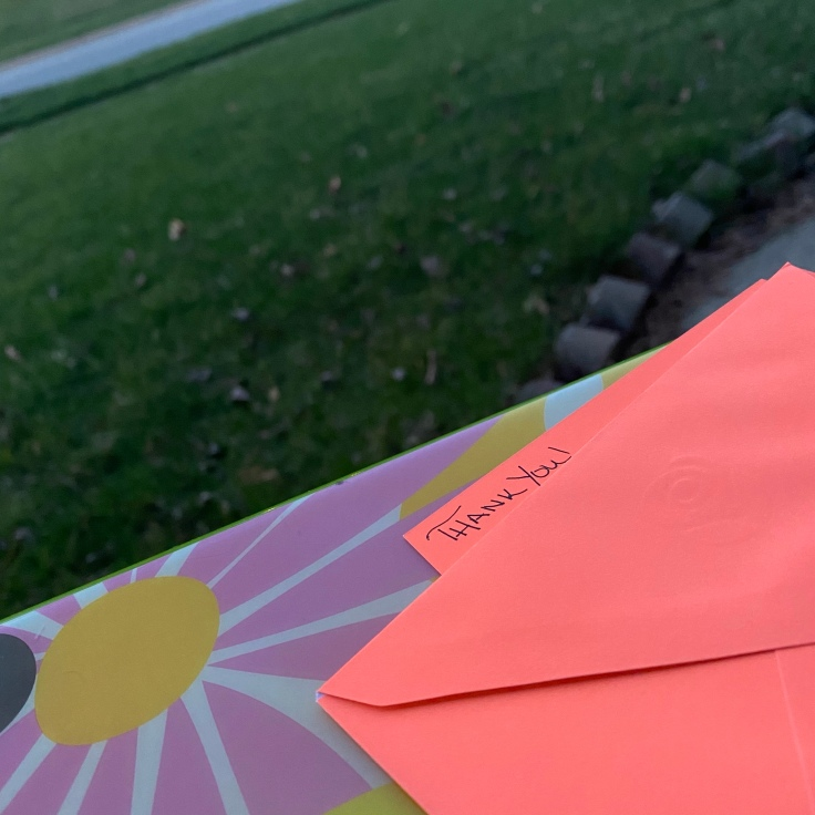 neon orange notecard with the handwritten words Thank You in the foreground, grassy yard in the background