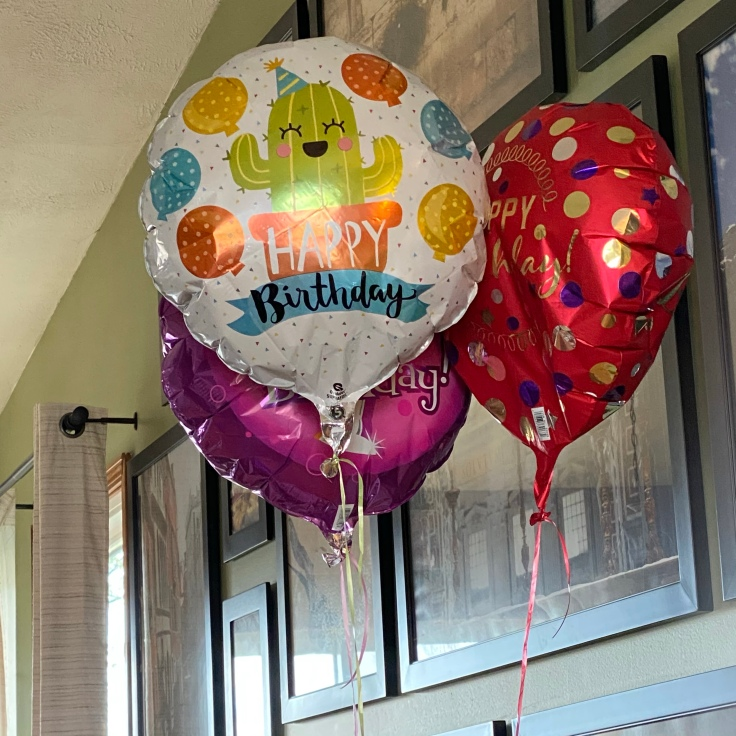 3 helium filled balloons on strings floating in a living room